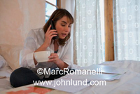 Picture of a busy woman of hispanic descent  working in her office at home. She is holding a cup of coffee in one hand and the phone in the other.  She is wearing a white blouse.
